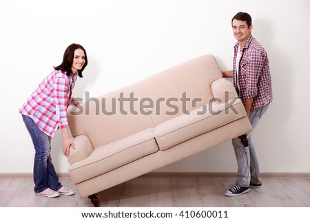 Young couple carrying sofa in their new house. - stock photo
