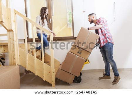 young couple carrying the boxes in new house - stock photo