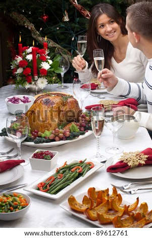 Young couple celebrates Christmas turkey dinner by the Christmas tree.
