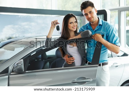 Young Couple Celebrating Purchase of a car In Car Showroom - stock photo