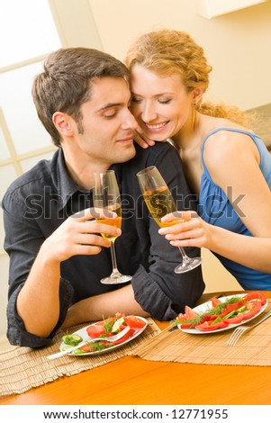 Young couple celebrating with champagne at home