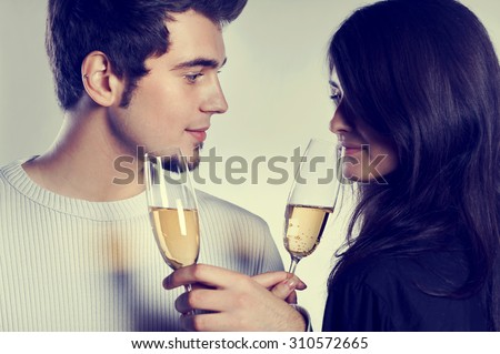 Young couple celebrating with champagne glasses - stock photo