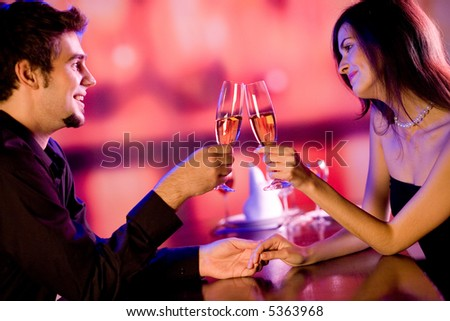 Young couple celebrating with champagne together - stock photo