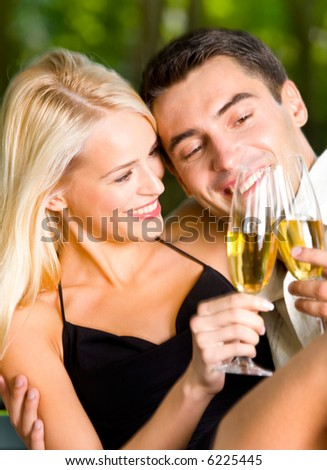 Young couple celebrating with champagne together, outdoors