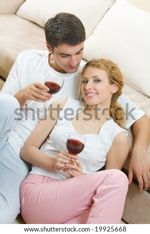 Young couple celebrating with red wine at home - stock photo