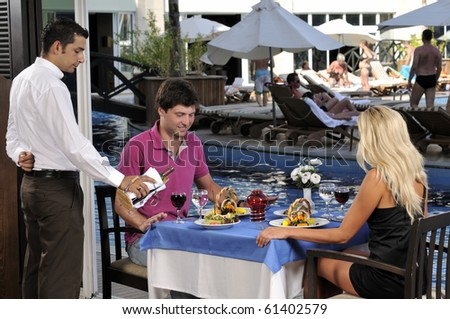 Young couple celebrating with red wine at restaurant - a series of RESTAURANT images.