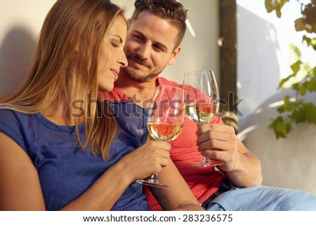Young couple celebrating with white wine together, outdoors. Young man and woman toasting wine glass while sitting close together in backyard. - stock photo