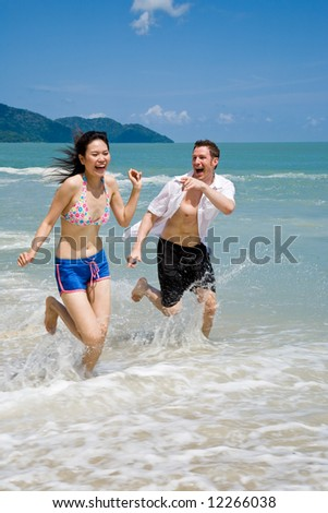 young couple chasing and running on a beautiful tropical beach