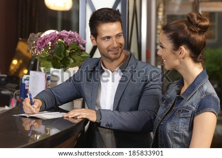 Young couple checking in at hotel reception smiling happy. - stock photo