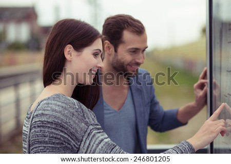 Young couple checking the timetable on a station for a train smiling as they scan the information with a finger - stock photo