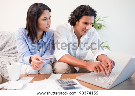 Young couple checking their bank accounts online - stock photo