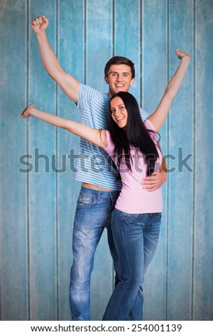 Young couple cheering at camera against wooden planks - stock photo