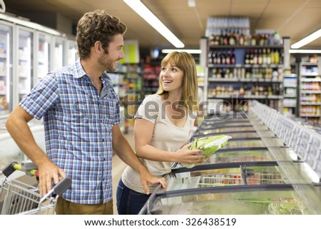 Young couple chooses frozen products in supermarket - stock photo