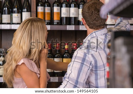 Young couple chooses the wine at supermarket - stock photo