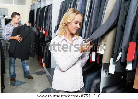 Young couple choosing business suit during clothing shopping at sales store - stock photo