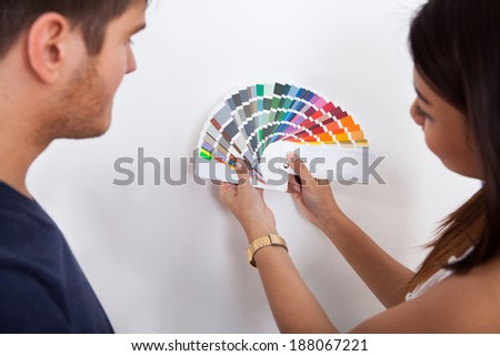 Young couple choosing color for wall from swatches at new home