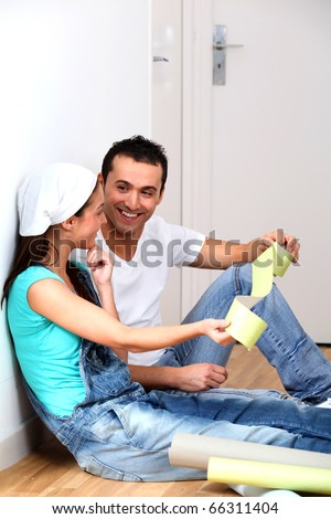 Young couple choosing color of wallpaper - stock photo