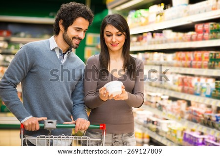 Young couple choosing food in a supermarket - stock photo