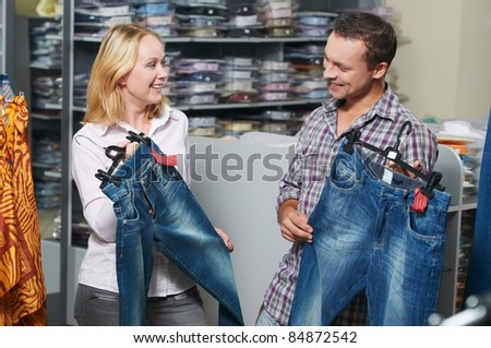 Young couple choosing jeans during clothes shopping at sales store - stock photo