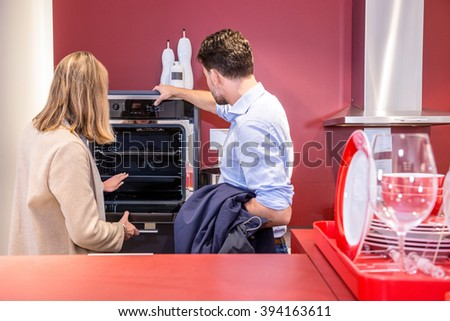 Young couple choosing microwave in household appliance section at hypermarket - stock photo