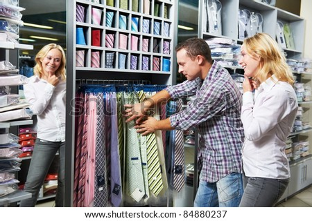 Young couple choosing necktie during clothes shopping at sales store - stock photo