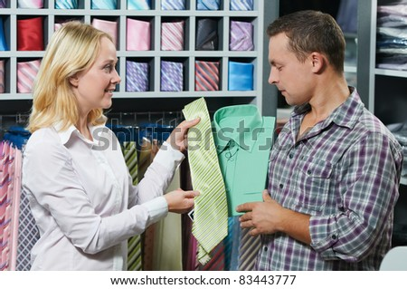 Young couple choosing shirt and necktie during clothes shopping at sales store - stock photo
