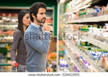 Young couple choosing the best food in a supermarket