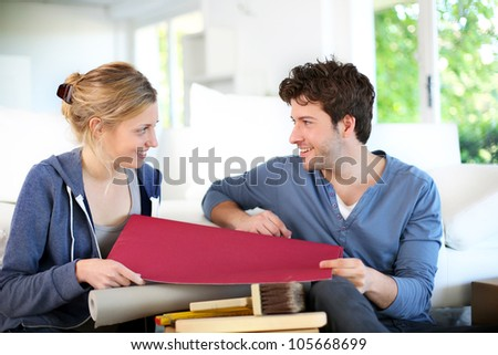 Young couple choosing wallpaper color for new apartment - stock photo