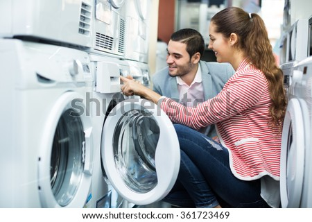 Young couple choosing washing machine in hypermarket and smiling  - stock photo