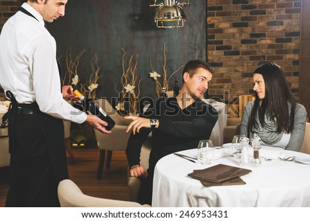 Young couple choosing wine in a restaurant - stock photo