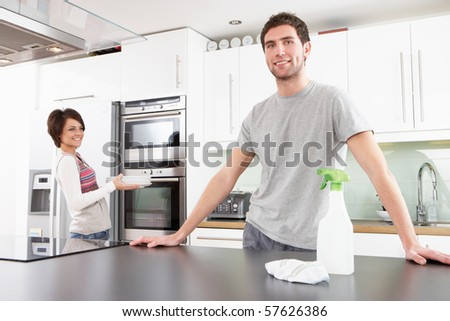 Young Couple Cleaning Cleaning Modern Kitchen - stock photo