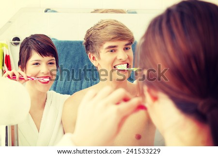 Young couple cleaning teeth together at bathroom. - stock photo