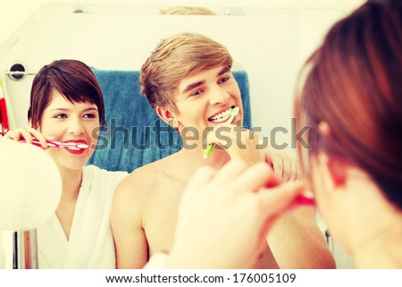 Young couple cleaning teeth together at bathroom. Focus on man.  - stock photo