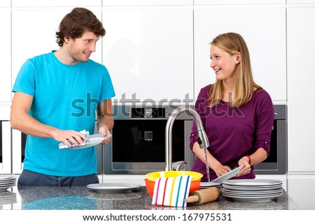 Young couple cleaning together after dinner - stock photo