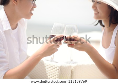 Young couple clinking glasses - stock photo