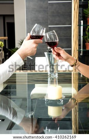 Young couple clinking with glasses of red wine  - stock photo