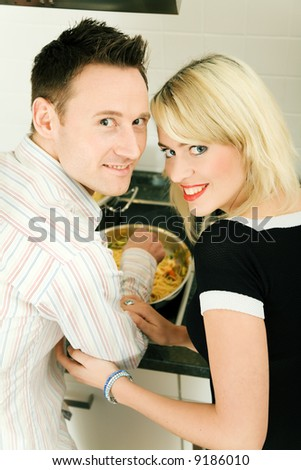 Young couple cooking, both looking into the camera - stock photo