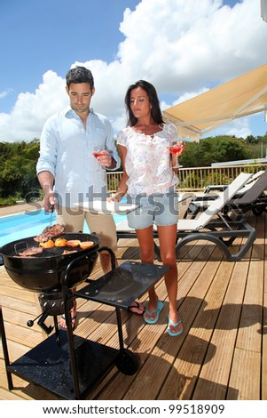 Young couple cooking dinner on barbecue grill