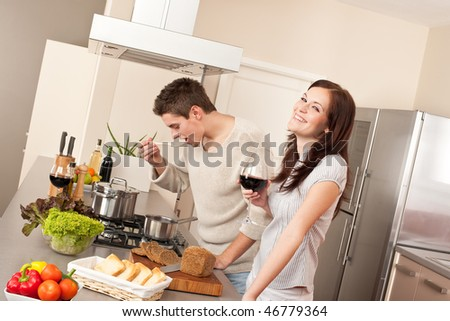 Young couple cooking in kitchen together drinking red wine - stock photo