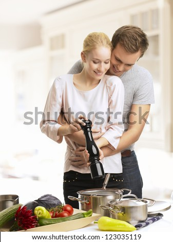 Young couple cooking in the kitchen together - stock photo