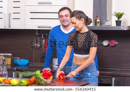 Young couple cooking - man and woman in their kitchen at home preparing vegetables for salad