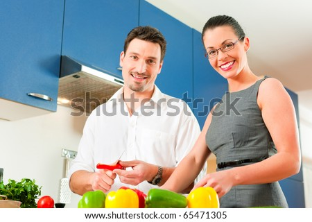 Young couple cooking - man and woman in their kitchen at home preparing vegetables for salad and pasta sauce