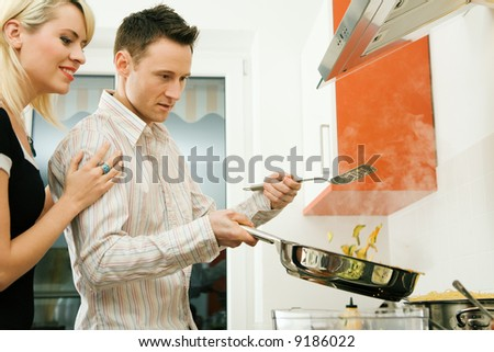 Young couple cooking. Selective focus on his face and cooking gear - stock photo