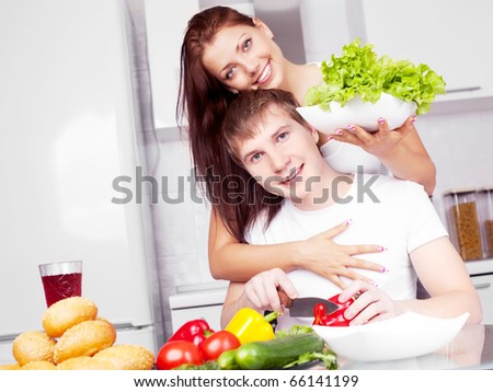 young couple cooking together in the kitchen at home (focus on the man) - stock photo