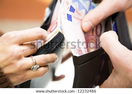 young couple counting money in their wallet - stock photo