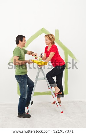 Young couple  creating their new home - drawing the conceptual blueprints - stock photo