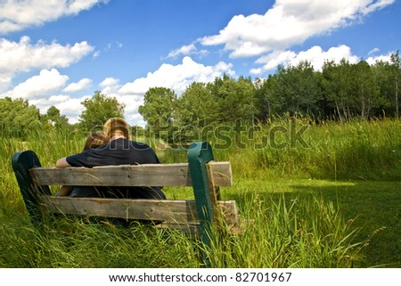 young couple cuddling on a park bench in front of a pond - stock photo