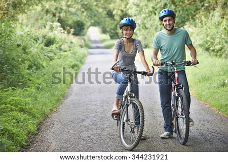 Young Couple Cycling Along Country Road