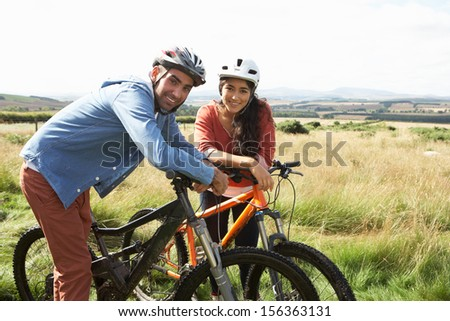 Young Couple Cycling In Countryside - stock photo