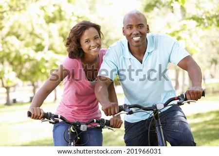 Young  couple cycling in park - stock photo